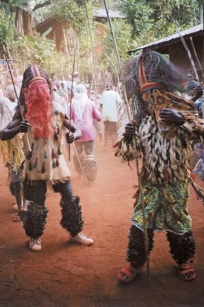 Männer mit Masken bei einer Totengedenkfeier