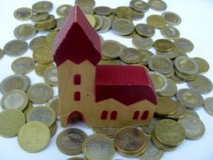 Kirche umgeben von Münzgeld