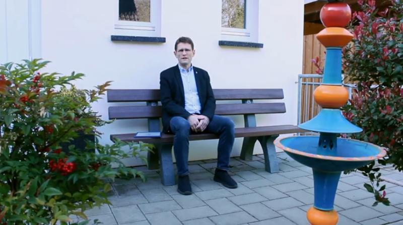 Pfarrer Thummes sitzt auf der Bank im Freien