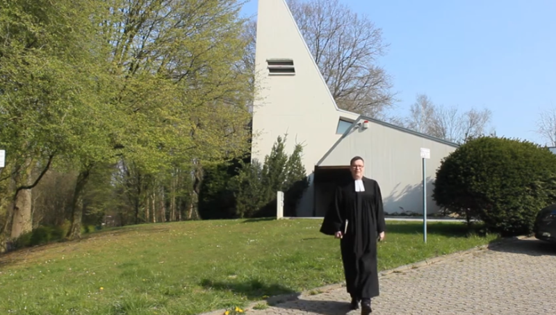 Pfarrer Müller geht über den Rasen vor der evangelischen Kirche am Kockskamp in Amern in Richtung Parkplatz und Straße